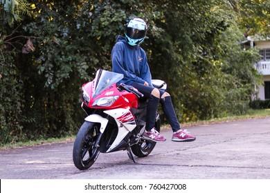 SISAKET,THAILAND - NOVEMBER 21 2017 : The man and Motorcycle at roadside which has beautiful street , Yamaha R15