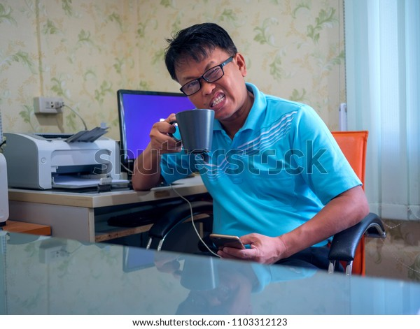 Sisaket,Thailand,01 June 2018;Angry Asian man holding coffee cup in office,Sisaket province,Thailand.