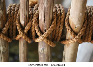 Sisal rope is crisscrossed over around bamboo sticks creating a fence.