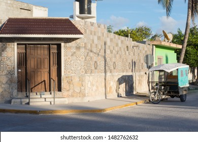 SISAL, YUCATAN/ MEXICO - JULY 30, 2019: Charming exterior architecture of street corner and brick street in port town of Sisal, Yucatan, Mexico on sunny afternoon