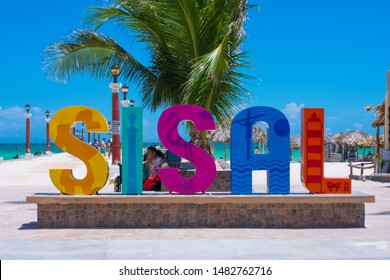 SISAL, YUCATAN, MEXICO - JULY 30, 2019: Colorful letters spelling the town's name welcome visitors at the public pier extending out on a turquoise sea along a white sand beach under a clear blue sky.