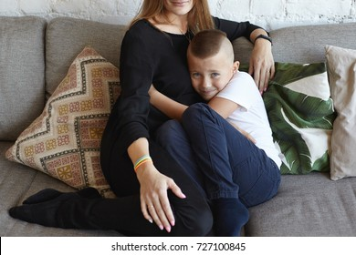 Sissy mama's boy sitting on grey couch and hugging his unrecognizable mother, seeking for her support against bullies, not able to stand up for himself, having miserable expression on his face