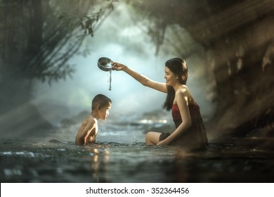 Sister and brother bathing in cascade, Thailand
