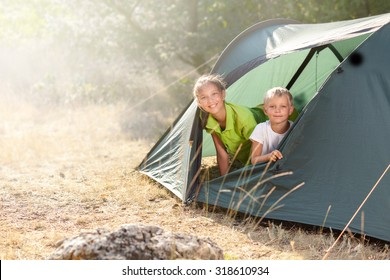 Sister and brother at camping in the summer morning