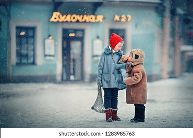"""Sister and brother are eating warm bread on frost in Russia in winter. Behind them there is a sign """"Bakery"""" written in Russian language. Image with selective focus and toning"""