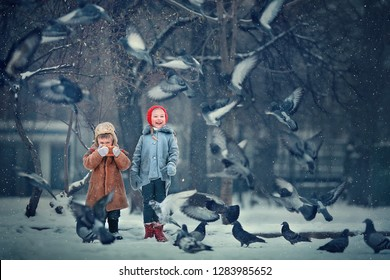 Sister and brother are feeding birds in Russia in winter. Image with selective focus and toning