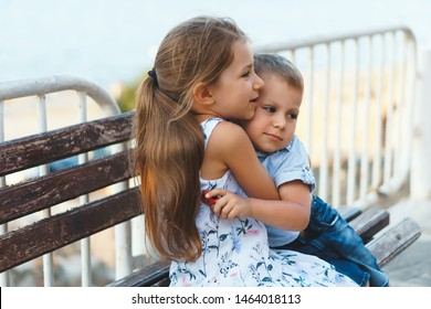 sister and brother hugging on wooden bench at fence