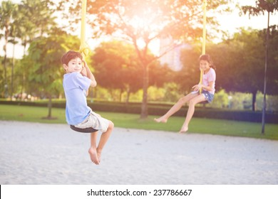 Sister and brother in playground swing outdoors