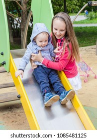 sister and brother playing on the Playgrou. The girl helps a little boy on a children's  slide. the concept of children's safety on the walk.   teen girl take care of toddlers.