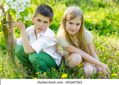 Sister and brother are resting a blooming garden in the spring. Children have fun in the apple orchard before sunset. Beautiful happy boy and girl in the flowered garden in the rays of the sunset