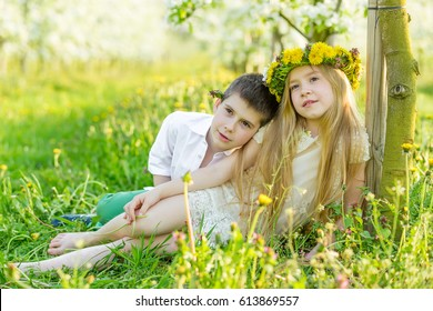 Sister and brother are resting a blooming garden in the spring. Children have fun in the apple orchard before sunset. Beautiful happy boy and girl in the flowered garden in the rays of the setting sun