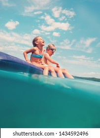 Sister and brother sitting on inflatable mattress and enjoying the sea water, cheerfully laughing when swim in the sea. Careless childhood time unusually water level shot image.