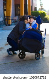 Sister or caregiver hugging and kissing little biracial disabled eleven year old boy in wheelchair outdoors