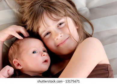 A sister giving her baby brother hugs
