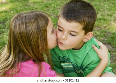 Sister giving her brother a kiss on the cheek