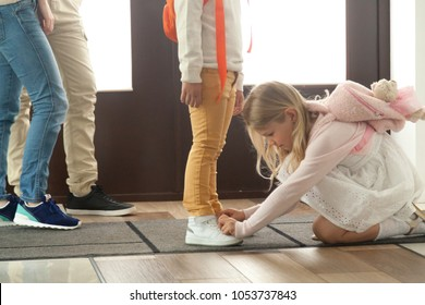 Sister helping brother to tie shoes preparing go to school, kid girl fasten shoelaces of child boy, little son and daughter getting ready for walk with parents, siblings friendship and good relations