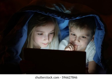 sister and her brother with laptop in bed