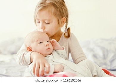 sister holding and kissing her newborn brother at the home
