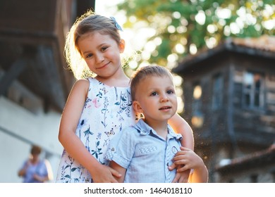 sister hugging younger brother in sunset light