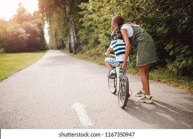 Sister and little brother learning to ride bicycle park having fun together