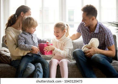 Sister presenting gift for little brother giving cute boy box with present, excited kid girl making surprise congratulating brother, happy family and children celebrating son birthday at home concept