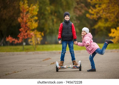 The sister rolls his brother on gyroscope in the autumn park.