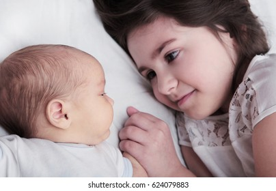 Sister Smiling Holding Hand of Newborn Baby Brother