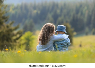 sister talking to brother and hugging him on grass