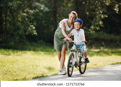 Sister teaching his little brother to ride bike