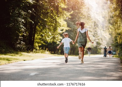 Sister teenager and little brother boy run their hands through park, sun light. Concept family sport. Back view.