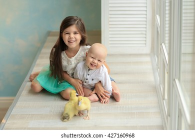 sister in a white shirt and blue skirt hugging baby brother in a white shirt and jeans sitting on the sill of the window, playing with two young chicks