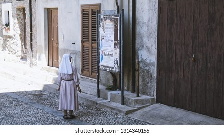 Sister who reads the obituaries in the streets of a small village, Calabria, Italy.