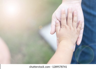 Sisterhood family relationship concept. Hands of little toddler girl on big sister to compare size of hand. Brother give me five with brotherhood.