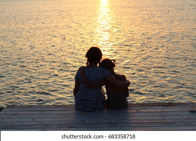 sisters with arms around each other at sunset