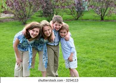 sisters and brothers outside in yard smiling