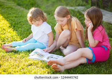 Sisters doing homework. reading in summer. Enjoying reading a book together outdoors.