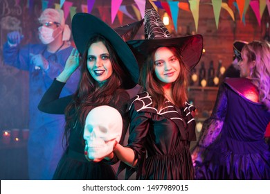 Sisters dressed up like witches at a halloween party holding a skull. Witches gathering. Halloween costume.