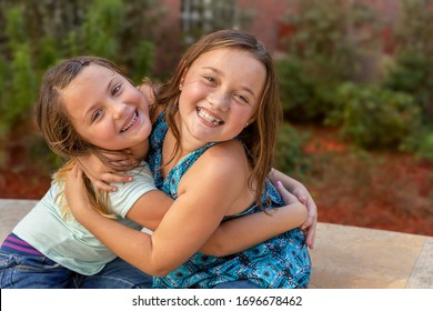 Sisters embrace each other in a warm hug while smiling at the camera. They are sitting together side by side, laughing out loud as they hold each other tightly.