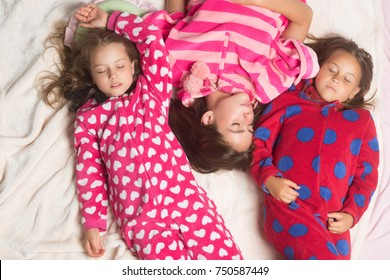 Sisters or friends in pajamas sleep in bed, top view. Good night, napping, bedtime, slumber, dream, sleepover concept