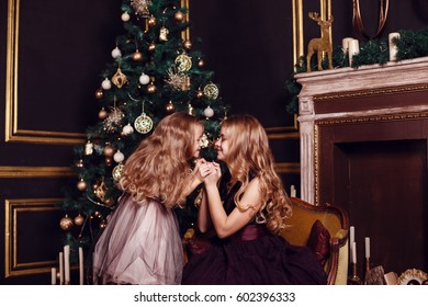 Sisters in front of the fir-tree and fireplace with candles and gifts. New year's eve. Christmas eve. Cozy holiday at the fir-tree with lights and gold decor.