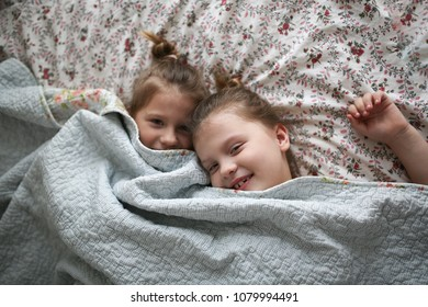 Sister's girls play and cuddle under a blanket, emotions. Concept childhood and related relationships, lifestyle and real interior, light tone, background with flowers, toning