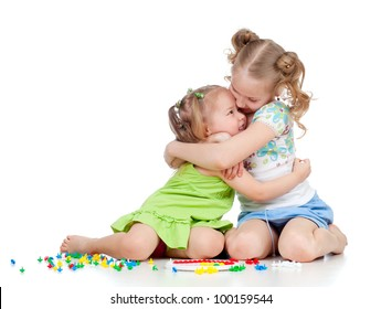 sisters girls playing and embracing over white background