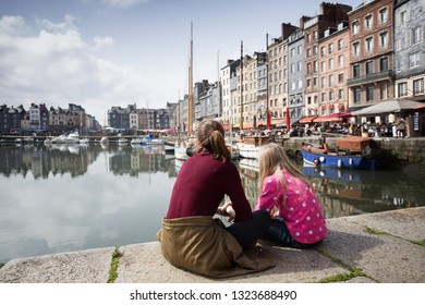 sisters girls sitting on background famous French city Honfleurr. Normandy, France