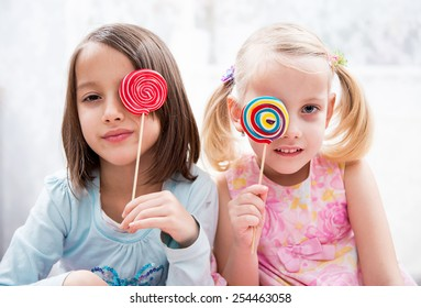 sisters have fun, colored lollipops