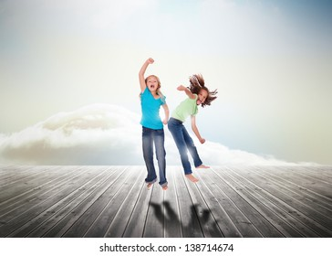 Sisters having fun jumping over wooden boards leading out to the horizon