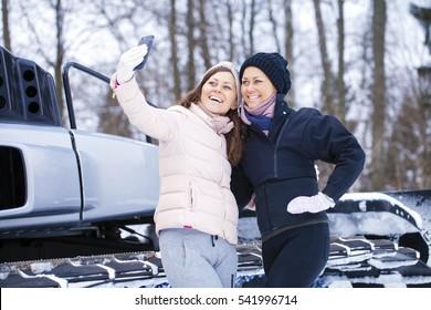 Sisters having selfie photo on ski resort