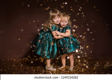 sisters hugging each other in Christmas decoration falling golden confetti background