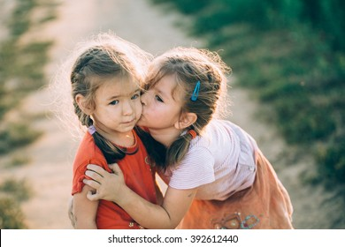 Sisters kissing and laughing in the summer outdoors