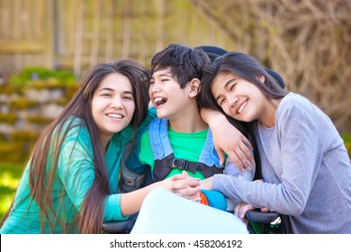 Sisters laughing and hugging disabled little nine year old  brother in wheelchair outdoors