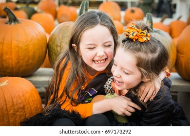 Sisters laughing in pumpkin patch